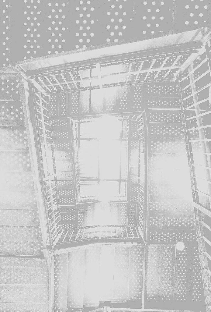 The view looking down the central space of a set of metal staircases.