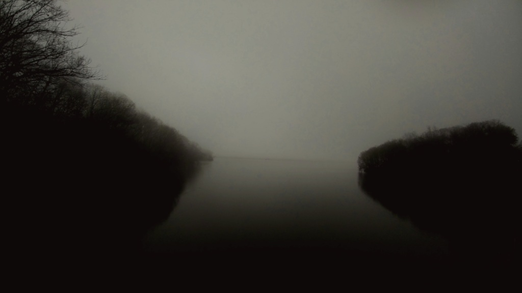 A great body of water, bordered on either side by tree-lined hills, shrouded in misty darkness.