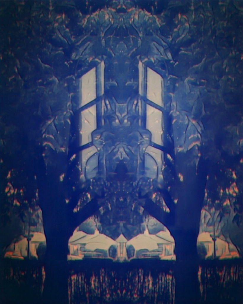 An artfully altered photo of mirror-imaged trees, hedge, reflections to offer a dreamlike, psychedelic image.