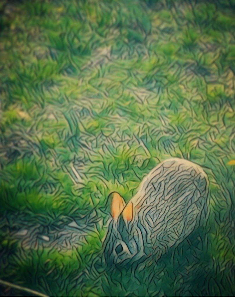 An artfully altered photo of a rabbit nibbling grass.